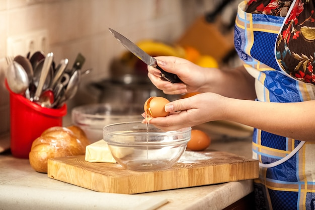 Photo gros plan d'une femme craquant des œufs avec un couteau