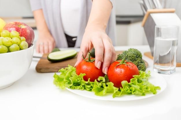 Photo gros plan d'une femme cueillant des tomates fraîches de la table dans la cuisine