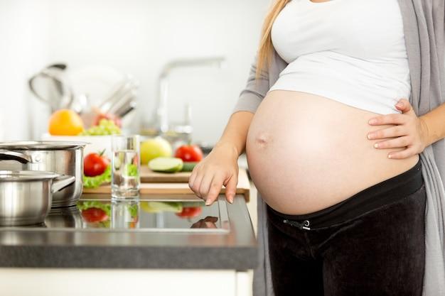 Photo gros plan d'une femme enceinte allumant une cuisinière électrique