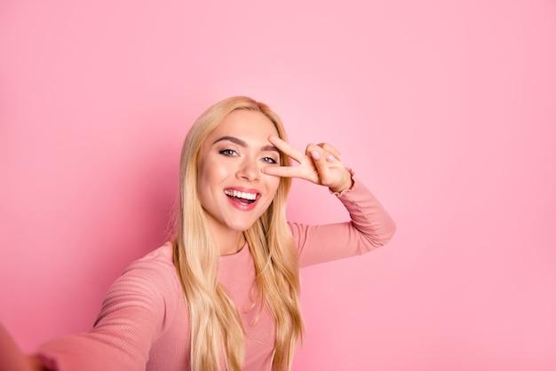 La photo en gros plan d'une femme heureuse prenant selfie et montrant deux doigts