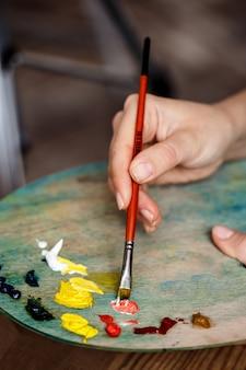 La photo en gros plan d'une femme mélangeant des peintures à l'huile sur palette