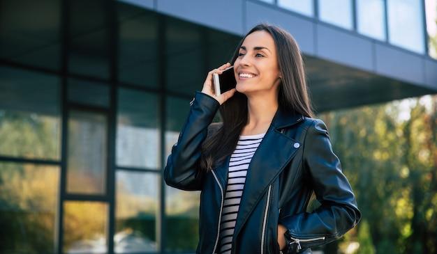 Photo en gros plan d'une femme moderne séduisante aux longs cheveux châtains, qui parle au téléphone dans la rue de la ville, regarde vers la gauche et sourit