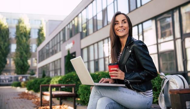 Photo en gros plan d'une femme occupée assise sur un banc à l'extérieur avec son ordinateur portable, tenant une tasse de café rouge et regardant par-dessus la caméra avec un large sourire
