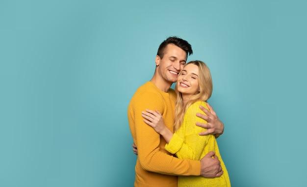 Photo en gros plan d'une femme parfaite et d'un bel homme aux yeux fermés, qui s'embrassent et sourient de joie.