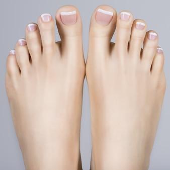 Photo gros plan d'une femme pieds avec pédicure française blanche sur les ongles
