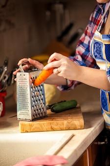 Photo gros plan de femme râper la carotte sur planche de bois