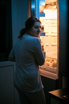 Photo gros plan d'une femme regardant dans un réfrigérateur tard dans la nuit