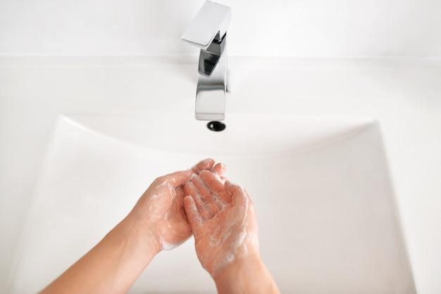 La photo en gros plan d'une femme se laver les mains dans un bassin propre blanc dans les toilettes à domicile, vue de dessus.