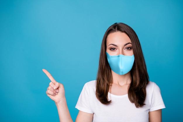Photo en gros plan d'une femme séduisante de bonne humeur dirigeant les doigts vers le haut de l'espace vide présentant la nouveauté de quarantaine covid porter un t-shirt blanc décontracté masque médical isolé fond de couleur bleu