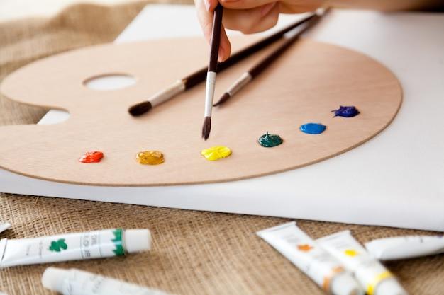 Photo en gros plan d'une femme tenant un pinceau et choisissant la couleur sur la palette