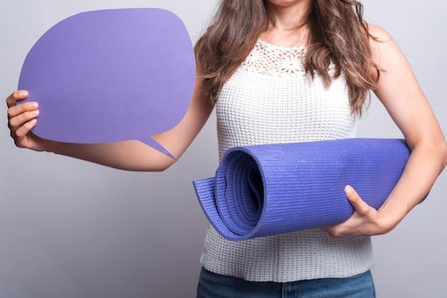 La photo en gros plan de femme tenant un tapis de yoga et une bulle de dialogue vide