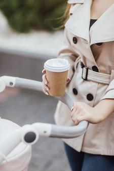 Photo en gros plan, femme tenant une tasse à café jetable et restant dans la poussette de bébé.