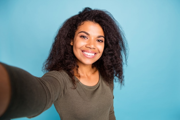 La photo en gros plan d'une fille afro-américaine joyeuse positive se sentir amusant en vacances les week-ends de temps libre font de selfie porter un pull de style décontracté isolé sur un mur de couleur bleue