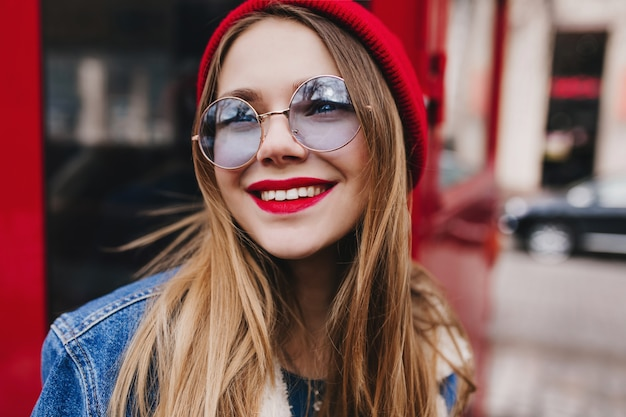 Photo en gros plan d'une fille blanche romantique porte des lunettes rondes regardant avec le sourire. jeune femme rêveuse avec un maquillage lumineux posant à côté du bus rouge.