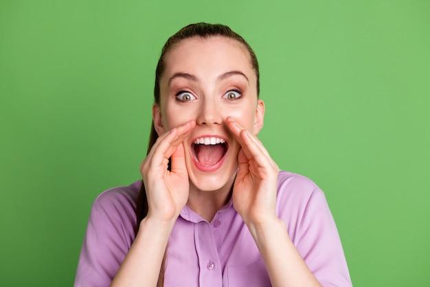 La photo en gros plan d'une fille étonnée folle entend une nouveauté incroyable tenir les lèvres de la bouche de la main crier partager un message porter une tenue lilas violette isolée sur fond de couleur verte