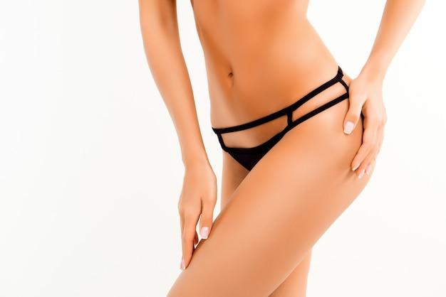 La photo en gros plan de la hanche de la femme galbée avec un pantalon noir