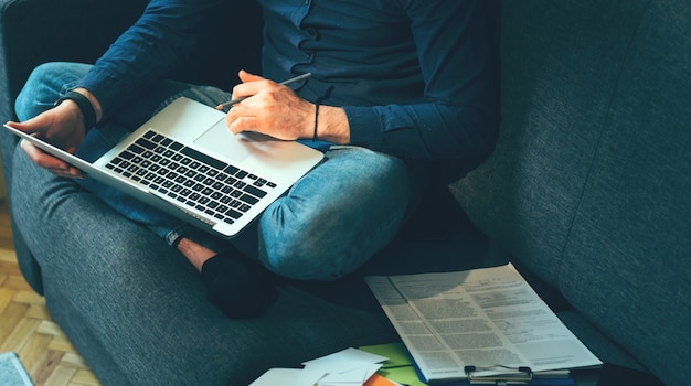 La photo en gros plan d'un homme d'affaires assis sur le canapé et travaillant avec un ordinateur et des documents