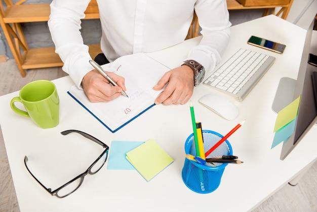 La photo en gros plan de l'homme d'affaires écrit le plan pour la journée dans le journal