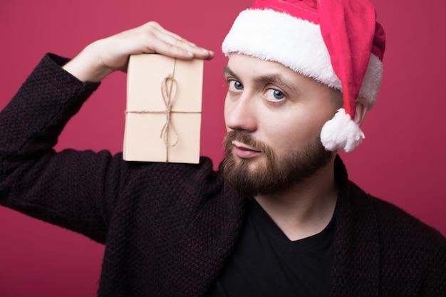 La photo en gros plan d'un homme barbu avec bonnet de noel tenant sur l'épaule un cadeau et sourire à l'avant sur un mur rose