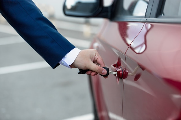 Photo gros plan de l'homme en costume ouvrant la porte de la voiture avec clé