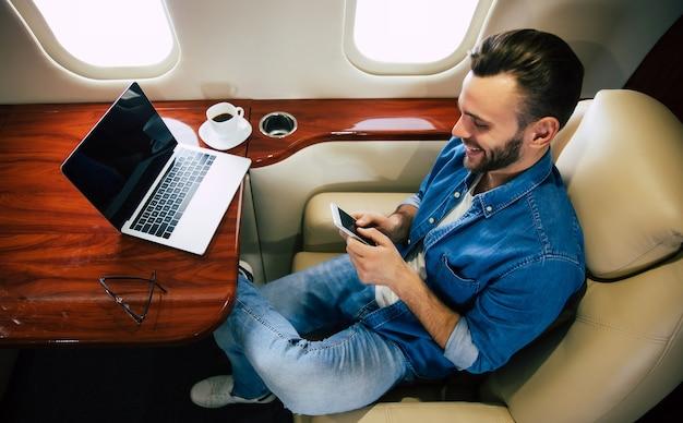 Photo en gros plan d'un homme gai dans une tenue décontractée, qui profite de son vol, assis dans son siège côté hublot et échangeant des messages sur son smartphone.