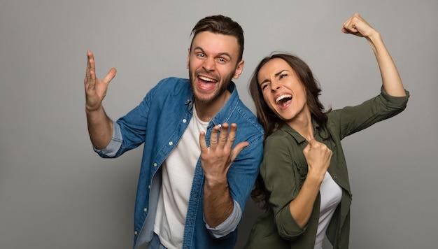 Photo en gros plan d'un homme heureux en vêtements en jean et d'une fille magnifique en tenue décontractée, qui montrent des gestes de réussite et se tiennent les mains dans les poings.