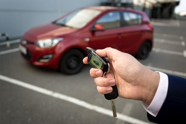 Photo gros plan d'un homme ouvrant une voiture avec une clé d'alarme à distance