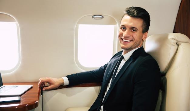 Photo en gros plan d'un homme séduisant en costume, assis de profil dans son siège côté hublot dans l'avion