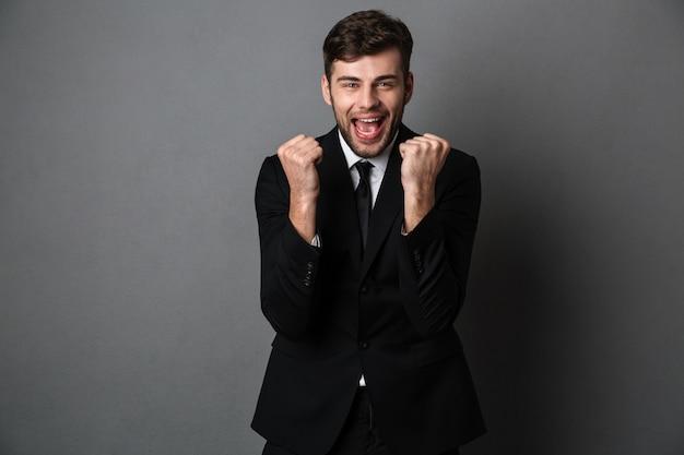 Photo en gros plan d'un homme séduisant heureux en costume classique montrant le geste du vainqueur,