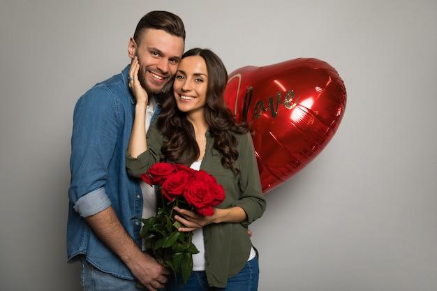 Photo en gros plan d'un homme séduisant, qui tient une boîte rouge dans ses mains, tandis que sa magnifique petite amie lui sourit après avoir reçu un bouquet de roses.