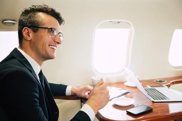 Photo en gros plan d'un homme séduisant en vêtements d'affaires, qui boit du café et a une petite conversation avec son collègue sur sa bande d'affaires, tout en volant en première classe.