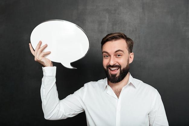 La photo en gros plan d'un homme souriant tenant une bulle de dialogue vide et regardant la caméra sur un espace de copie de mur gris foncé