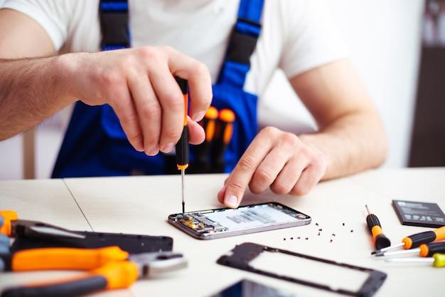 Photo en gros plan d'un homme spécialisé pendant qu'il répare un smartphone cassé sur son lieu de travail avec des outils professionnels