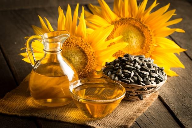 Photo gros plan de l'huile de tournesol avec des graines sur fond de bois. concept de produit bio et biologique.