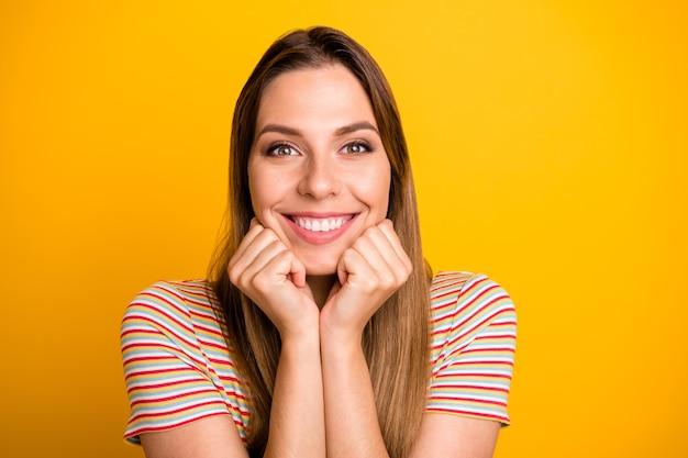 Photo gros plan d'une incroyable dame tenant le menton sur les mains ravi vue agréable montre mignon petit ami cadeau porter un t-shirt rayé décontracté mur de couleur jaune isolé