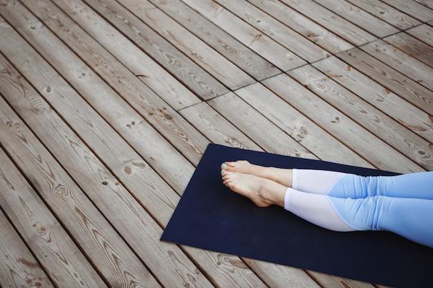 La photo en gros plan des jambes de la jeune fille sur fond de bois