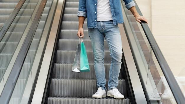 La photo en gros plan des jambes masculines en jeans avec des sacs à provisions alors qu'il est debout sur l'escalator dans le centre commercial