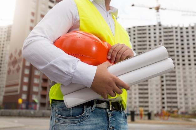 Photo en gros plan d'un jeune architecte posant avec un casque et des plans sur le chantier de construction