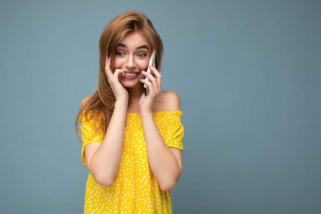 Photo gros plan d'une jeune femme blonde assez positive portant une élégante robe d'été jaune debout