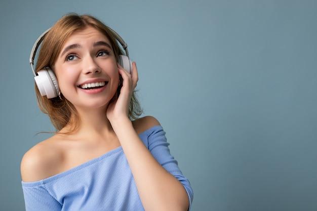Photo gros plan d'une jeune femme blonde souriante assez heureuse portant un haut court bleu isolé sur bleu