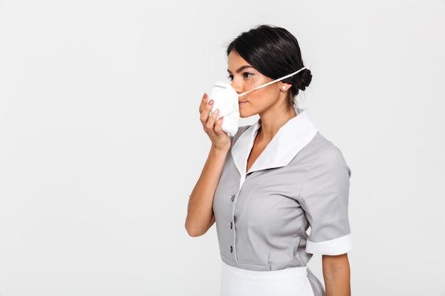 Photo en gros plan d'une jeune femme brune en uniforme mettant un masque de protection