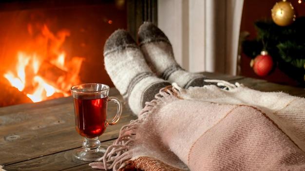 Photo gros plan jeune femme buvant du thé sous couverture à côté de la cheminée