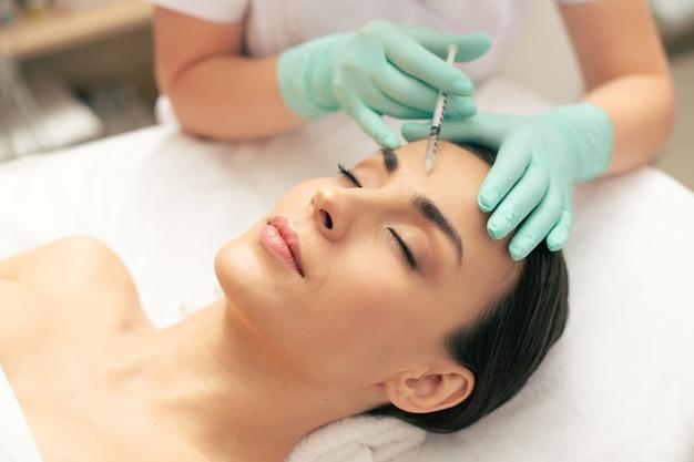 Photo en gros plan de la jeune femme calme allongée les yeux fermés et les mains dans des gants en caoutchouc faisant une injection dans la peau de son front