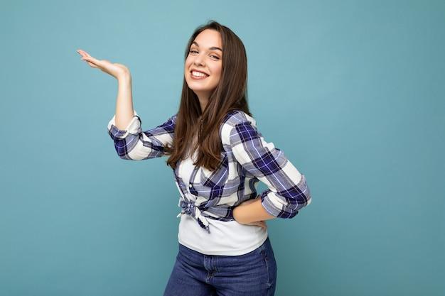 La photo en gros plan d'une jeune femme charmante et mignonne, heureuse et heureuse, tenant la main et montrant une publicité portant des vêtements décontractés isolés sur fond avec espace de copie.