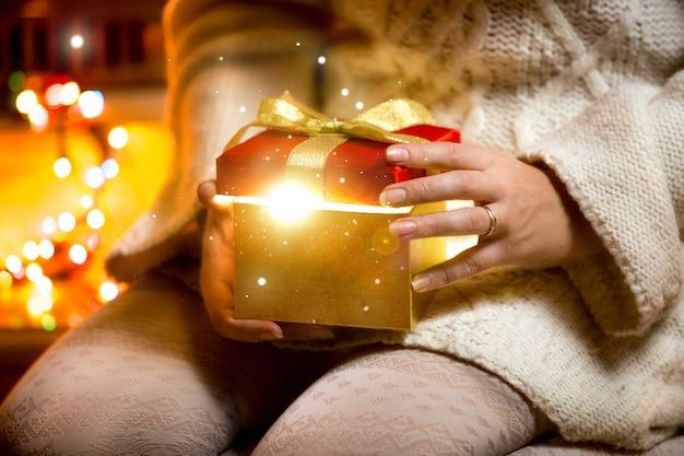 Photo gros plan d'une jeune femme ouvrant une boîte-cadeau avec de la lumière qui en sort