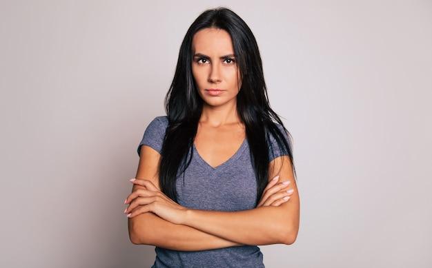 Photo en gros plan d'une jeune femme sérieuse aux longs cheveux noirs, qui se tient devant la caméra les bras croisés et regarde de côté