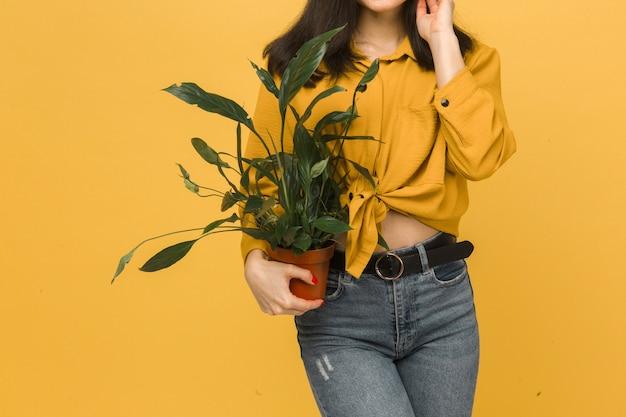 La photo en gros plan de la jeune femme tient la plante. porte une chemise jaune et un jean, fond de couleur jaune isolé