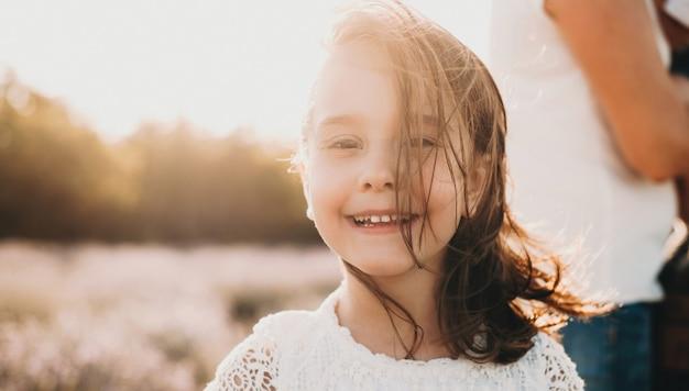 La photo en gros plan d'une jeune fille de race blanche souriant à l'avant avec un champ de lavande sur fond