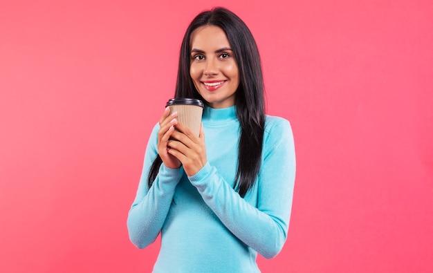 Photo en gros plan d'une jeune fille souriante dans un pull à col roulé turquoise, qui tient une tasse de café dans ses mains et regarde dans l'appareil photo