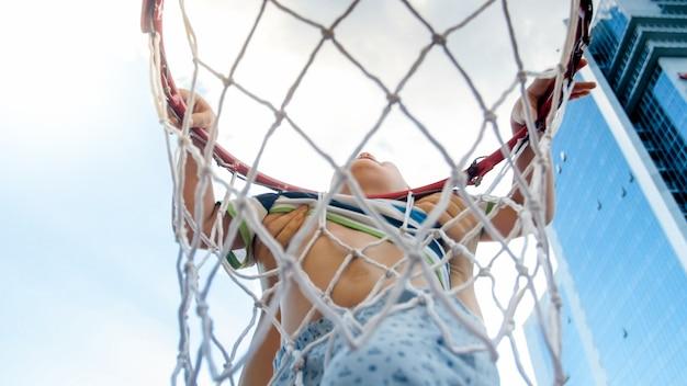 Photo gros plan d'un jeune garçon de 3 ans actif tenant sur un anneau de filet de basket-ball. concept d'enfants actifs et sportifs. santé des enfants de la nouvelle génération